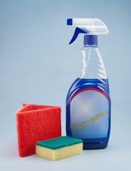 Cleaning spray bottle with sponge and fibre on blue background