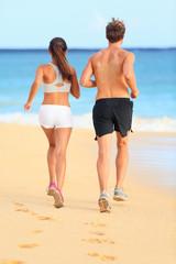 Jogging running young fitness couple on beach sand