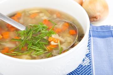 Gemüsesuppe in großem Topf mit Zwiebeln und Kräutern