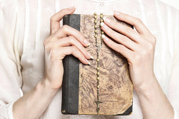 Young woman holding a Holy Bible and rosary