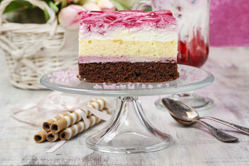 Layer cake with pink icing on a glass cake stand