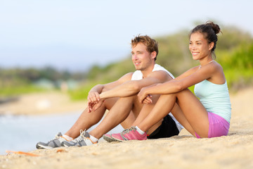 Sporty runners resting sitting before run on beach