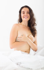 Happy nudity woman sitting in bed