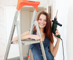 Happy woman in dungarees with drill