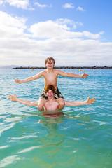 boys having fun in the  sea playing piggyback