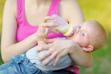 Baby drinking milk from bottle in mother hands