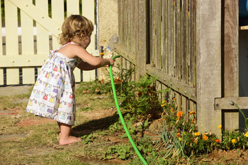 Kid watering flowers in the garden