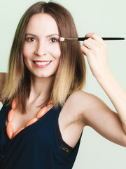 Woman applying eyeshadow with makeup brush