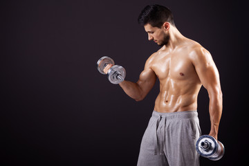 Fitness man lifting dumbbells on black background