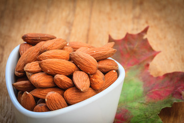 Almonds in bowl on autumnal background