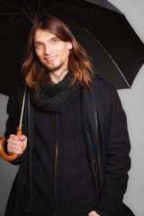 Men winter fashion. Man in black coat with umbrella