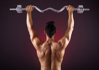 Rear view of a fitness man lifting weights with curl bar