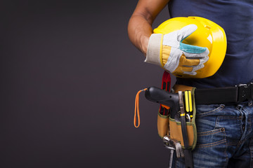 Close up of a worker with toolbelt and helmet against black back