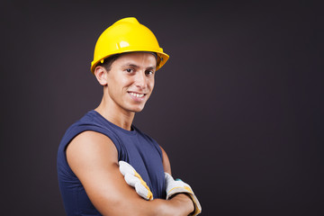 Portrait of a smiling young worker against black background