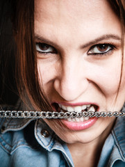 Angry woman mad girl biting metal chain