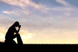 Woman Sitting Down in Prayer Silhouette