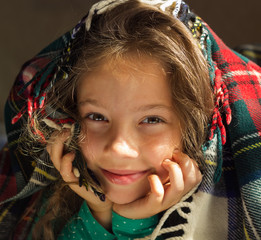 closeup Portrait of cute smiling girl look out from plaid