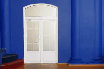 White modern door indoors and a lot of copyspace on deep blue