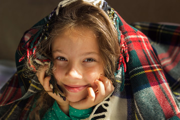 Portrait of adorable smiling baby girl look out from plaid