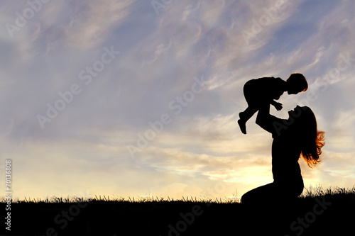 Silhouette of Happy Mother Playing Outside with Baby - 70136808