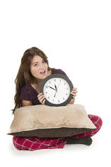 Cute young girl wearing pajamas holding big round clock