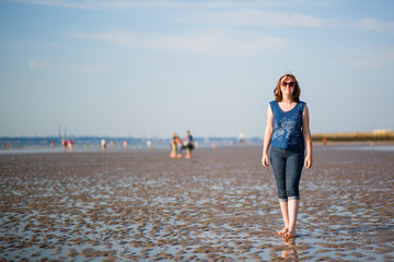 Beautiful woman walking on the beach at low tide
