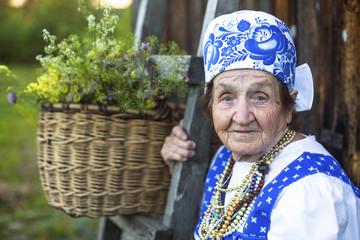 Old woman in Slav folk costume near a village house.
