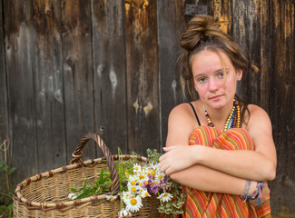 Girl in a rural setting with a basket of wild flowers.
