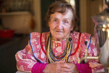 Elderly grandmother in ethnic clothes sitting in his house.