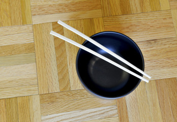 Black bowl with chopsticks on wooden table