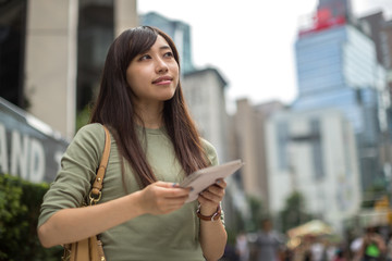 Young Asian woman in city using tablet pc computer