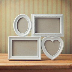Picture frame on wooden table over vintage background