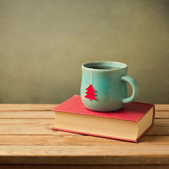 Christmas tea cup and book on wooden table
