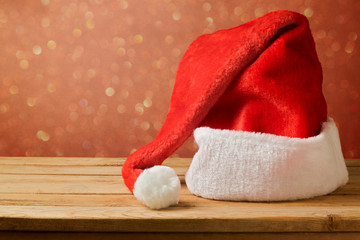 Santa Claus hat on wooden table over bokeh background