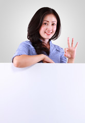 Smiling young business woman showing blank sign board