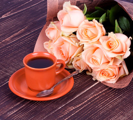 Cup of coffee and roses over wooden background