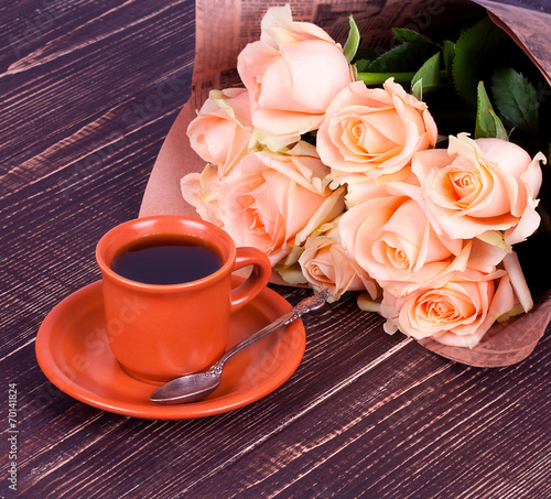 canvas print picture Cup of coffee and roses over wooden background