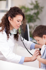 female doctor examines the boy with stethoscope