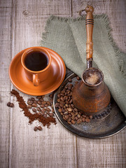Coffee turk and cup of coffee on wooden background