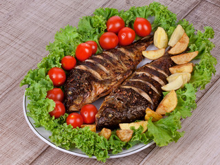 Whole grilled fish carp with potatoes, tomatoes cherry and lemon