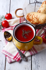 Homemade tomato juice in color mug, bread sticks, spices and