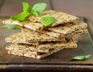 Dry flat bread crisps with herbs on a wooden board
