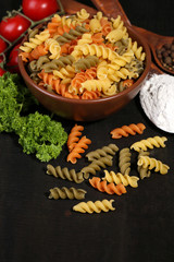 Composition of colorful pasta in bowl, fresh tomatoes, parsley