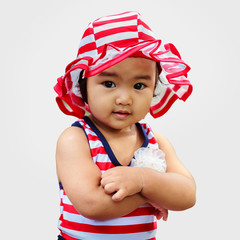 Confident asian cute baby in hat with arm cross
