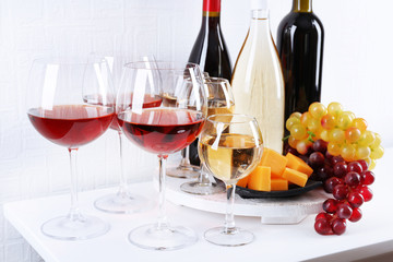 Bottles and glasses of wine, cheese and ripe grapes