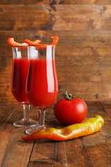 glasses of tasty tomato juice and pepper on wooden table