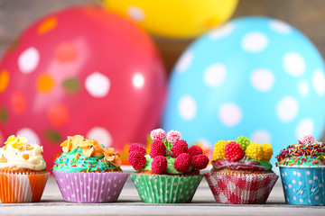 Delicious birthday cupcakes on table on bright background