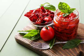 Sun dried tomatoes in glass jar, basil leaves
