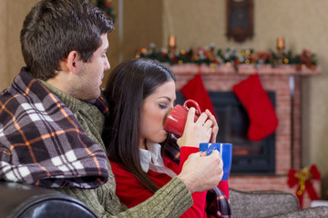 beautiful young couple drinking tea in Christmas night
