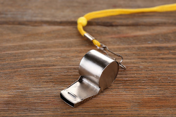Sport metal whistle on wooden background